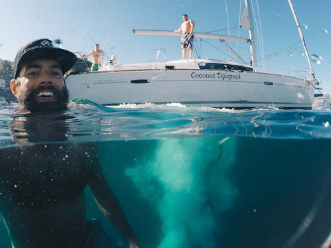 man with beard swimming by sailboat