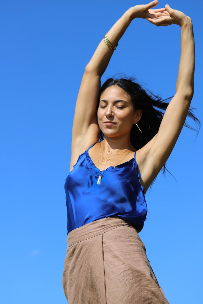 girl stretching in front of blue sky with layered delicate gold jewelry