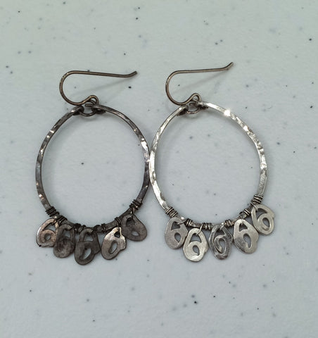 One tarnished silver earring next to a clean silver earring