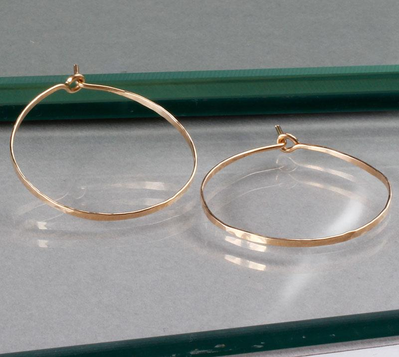 small gold endless hoop earrings on green glass