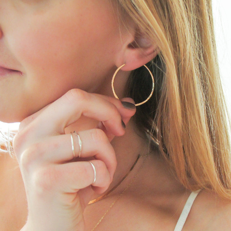 small gold endless hoop earrings on ear with fingers holding to show scale