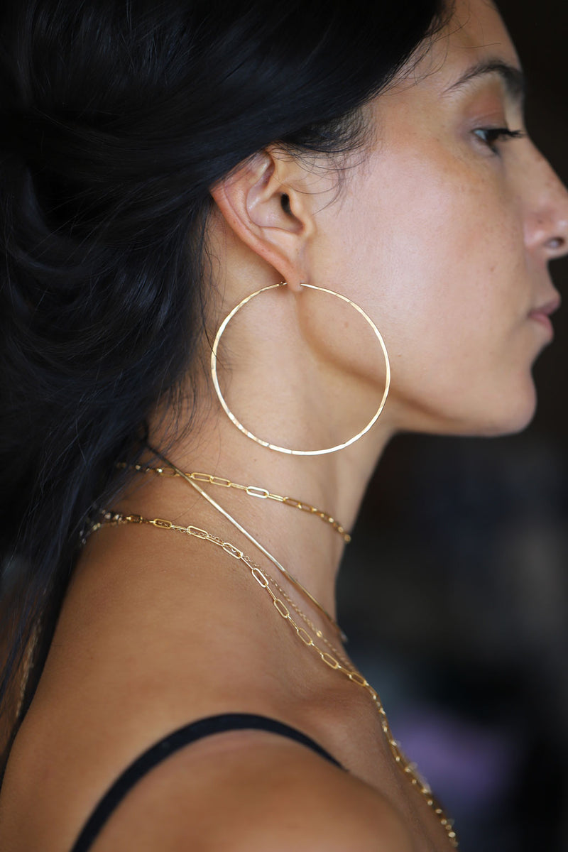 Brunette woman wearing layered gold necklaces and thin gold hoop earrings