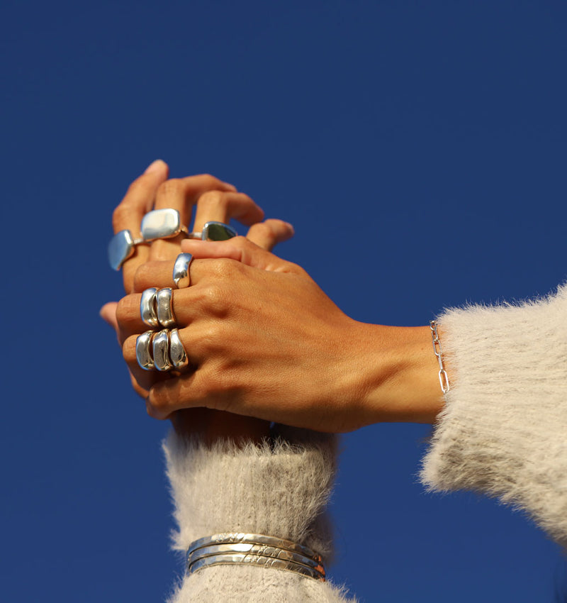 Woman's hands wearing big silver rings silver link bracelet and three thick bracelets