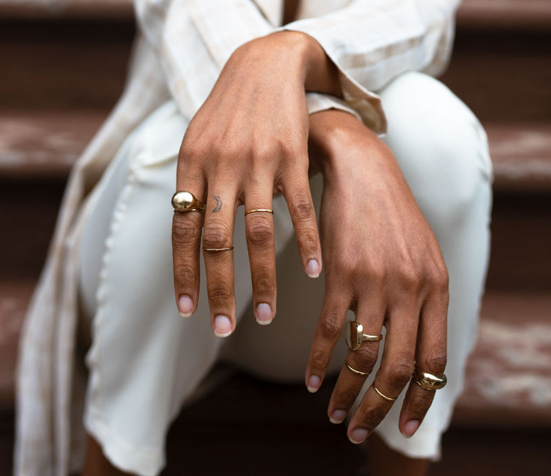 black woman hands close-up wearing globe ring thin gold stacking rings plateau ring and curved ring sitting on stairs