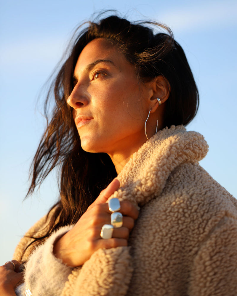 Brunette woman wearing Irregular silver hoops, hug hoop, big rings, and a wool jacket