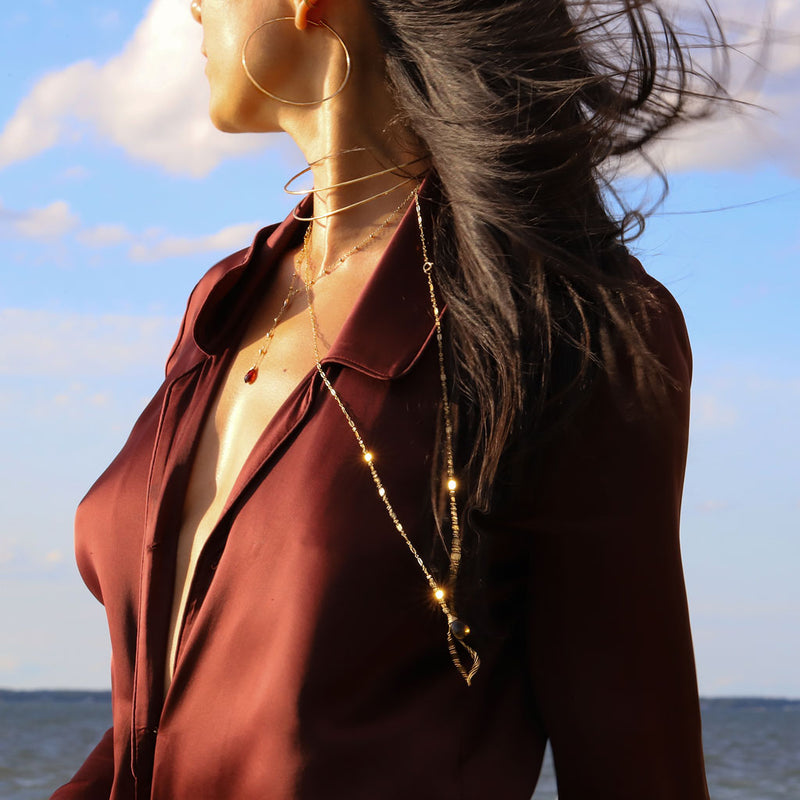 Brunette woman wearing gold wrap necklaces with garnet gemstones and a red shirt on the beach