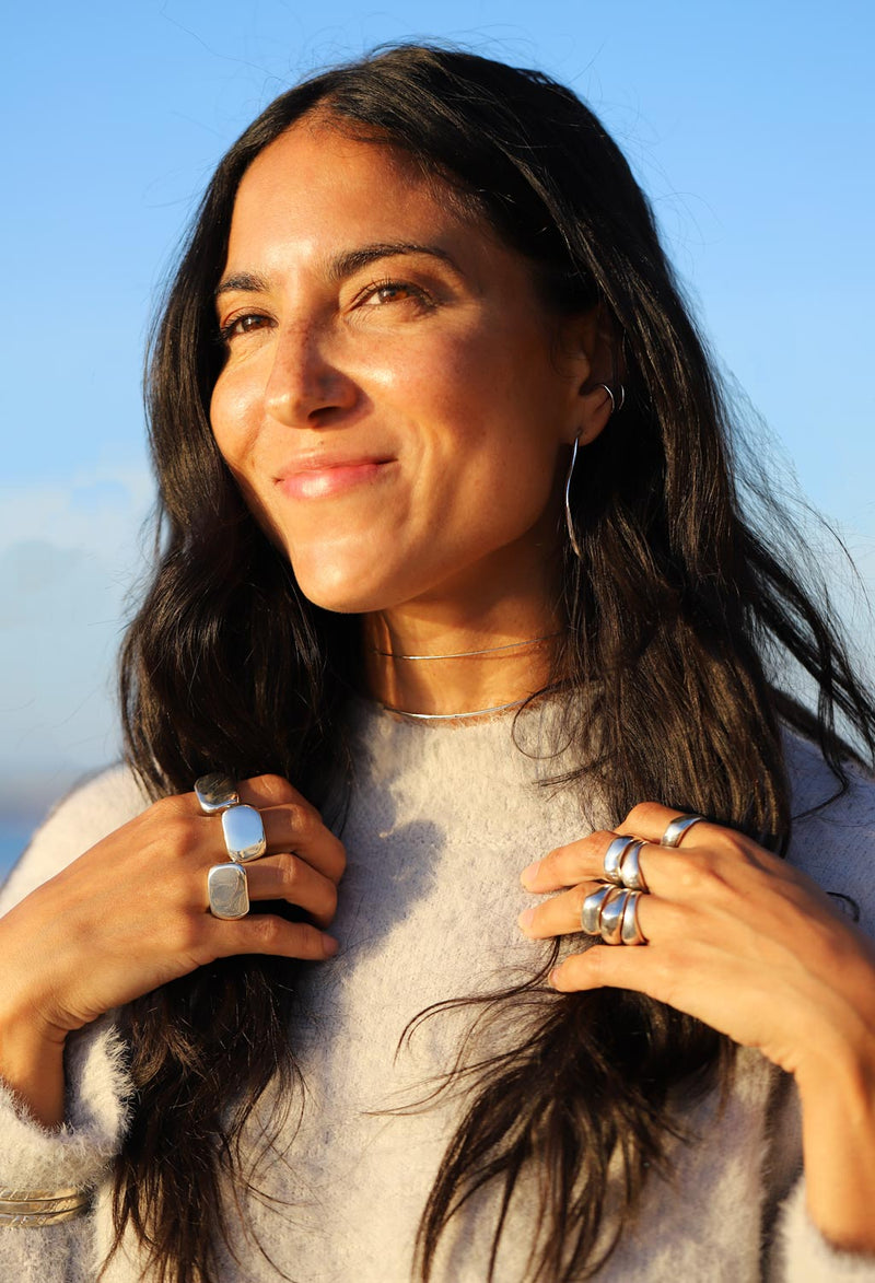 Brunette woman wearing big silver rings, hoops, and necklaces