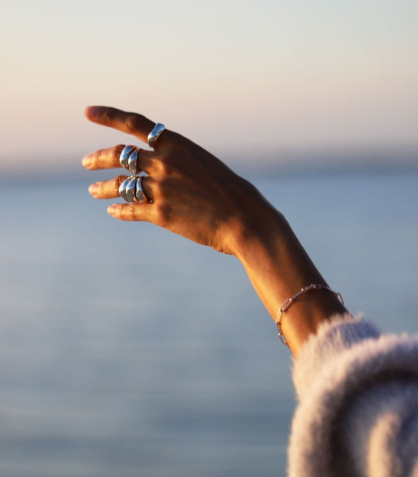 Woman's hand wearing six silver big rings and a silver link bracelet at the ocean