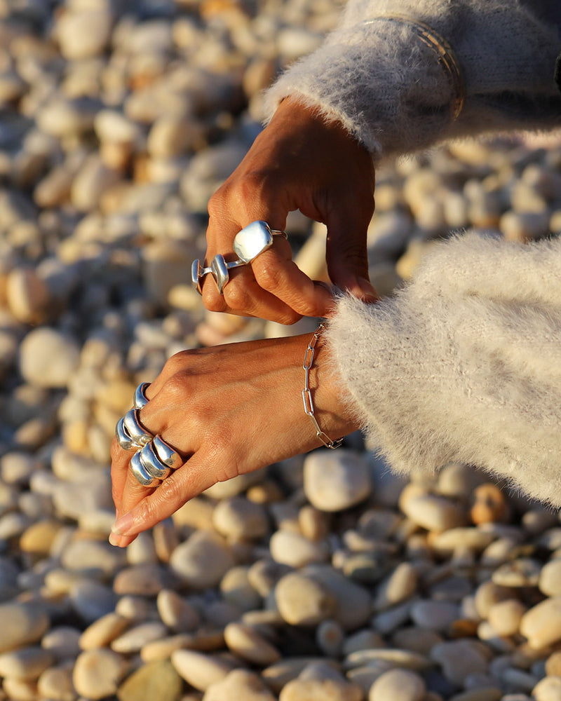 Woman's hands wearing big silver rings and silver link bracelet at the beach.