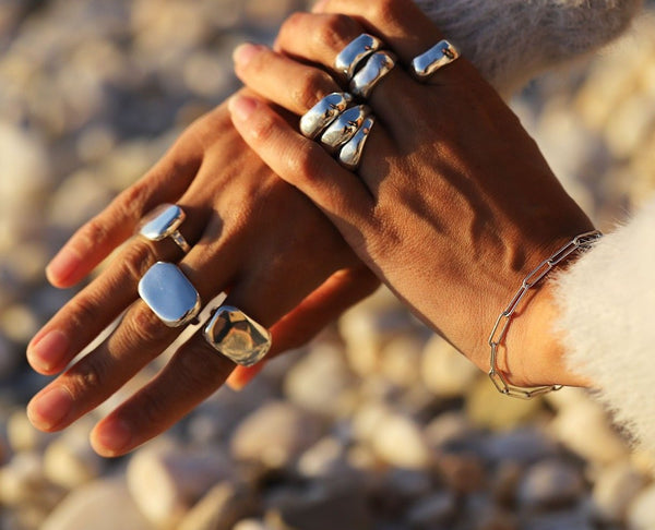 Woman's hands closeup wearing big silver rings and silver link bracelet at the beach.