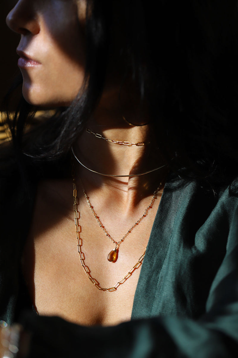 Brunette woman wearing four layered gold necklaces, and green shirt