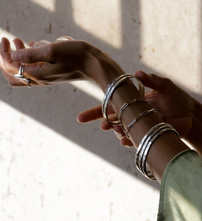 Woman wearing big silver rings, link bracelets, thick silver bracelets, and a green blouse