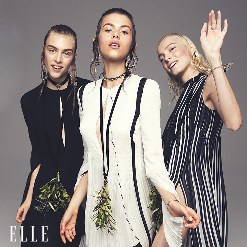 3 elle models in black and white dresses wearing multiple pieces of jewelry on ears neck and wrists