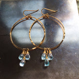 blue topaz and 14k gold filled hammered hoop earrings on steel hammering block