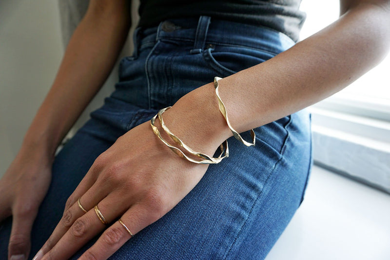 gold wavy bangles and gold stacking rings by delia langan jewelry