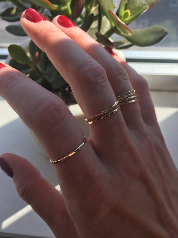 red nails hand wearing 14k gold filled wavy and flat rings on index middle and ring fingers with a green plant on background
