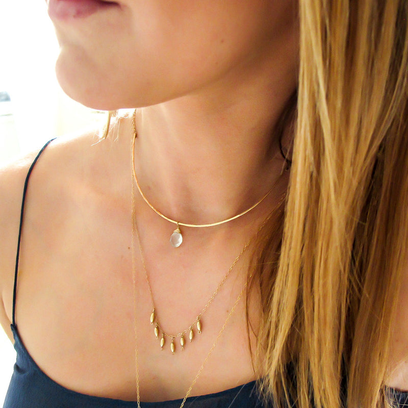 blond woman on a navy blue top wearing a 14k gold filled gold grain necklace