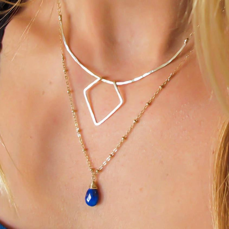 gold geometric necklace layered with delicate blue lapis pendant