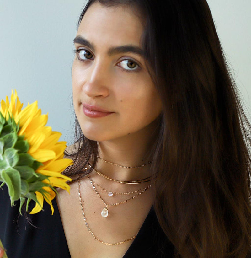 girl with layered moonstone necklaces holding sunflower