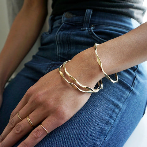 gold wavy bangles by delia langan jewelry