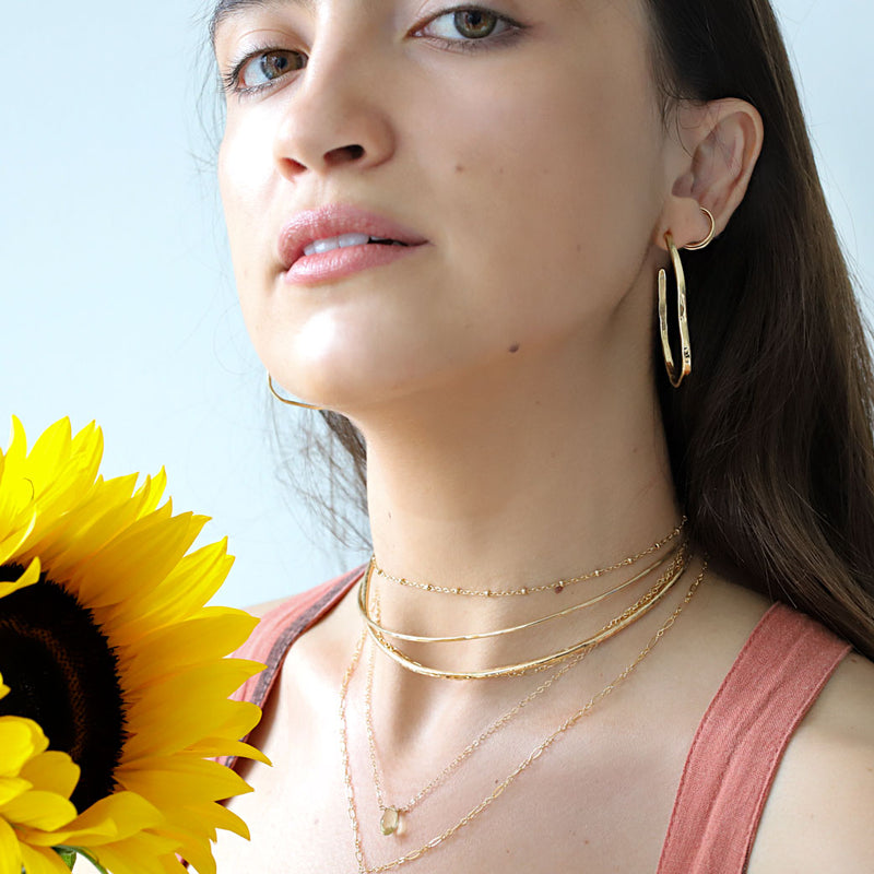 brunette wearing layered gold choker necklaces a lemon quartz short gemstone necklace and brass maeve bold hoop earrings