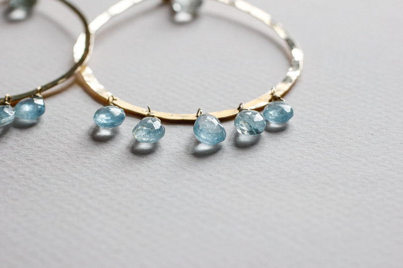 gemstone closeup of 14k gold filled blue aquamarine chandelier gemstone hoops on grey surface