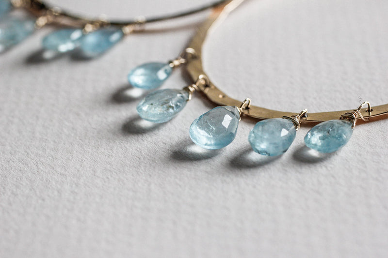 gemstone high closeup of 14k gold filled blue aquamarine chandelier gemstone hoops on grey surface