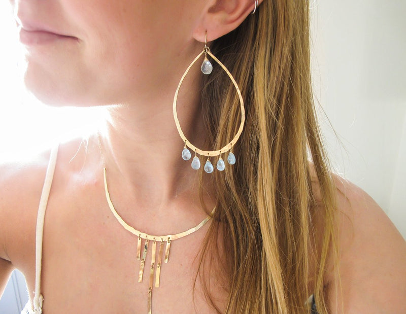blond woman wearing 14k gold filled blue aquamarine chandelier gemstone hoops