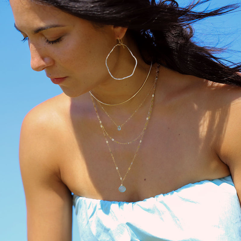brunette on a blue top against wind looking down wearing 14k gold filled potatohead hoop earrings