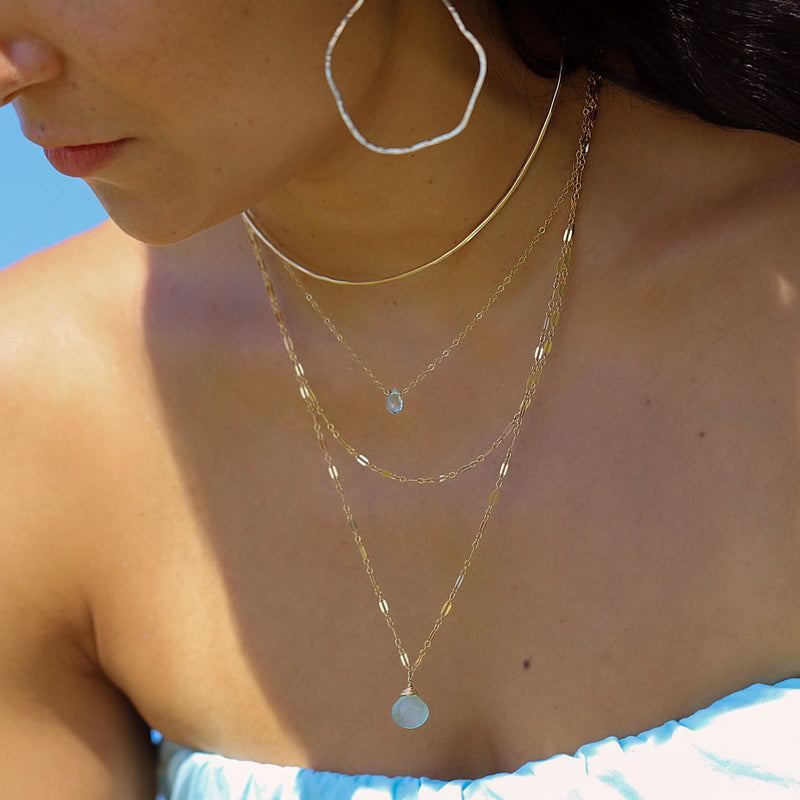 girl with delicate layered gold and blue gemstone necklaces.