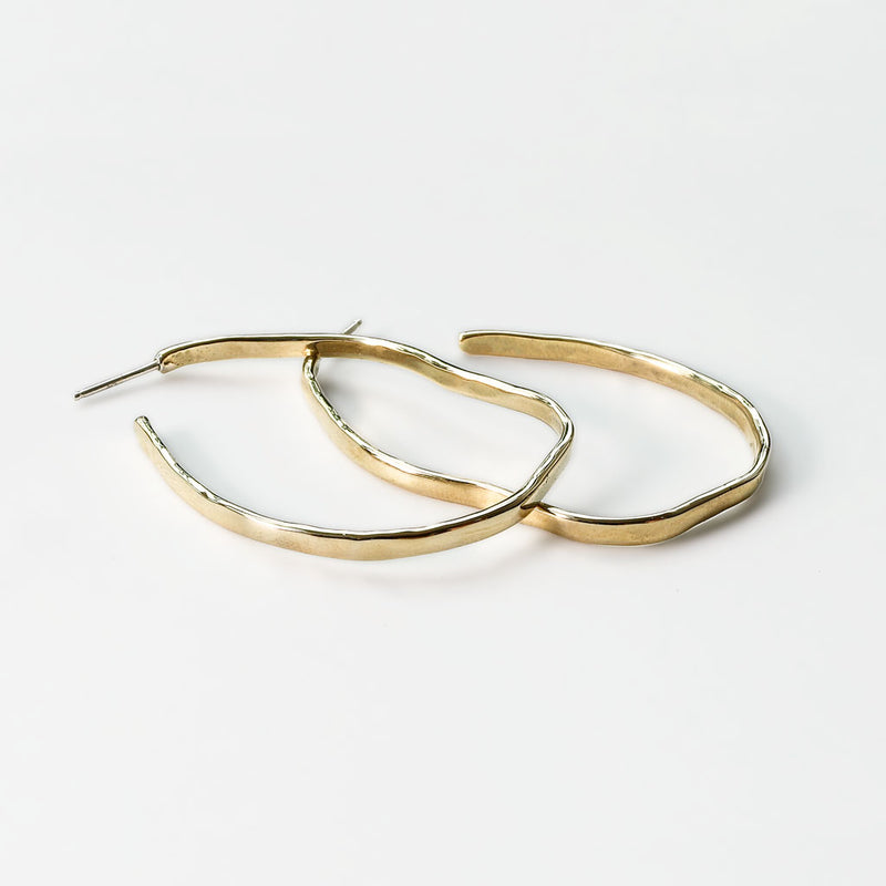 brass with sterling posts maeve bold hoop earrings on white surface