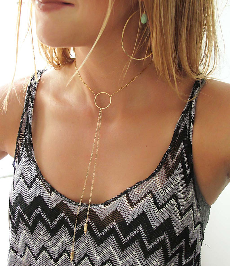 blond woman on a black grey and white stripes top wearing a 14k gold filled bolo y necklace