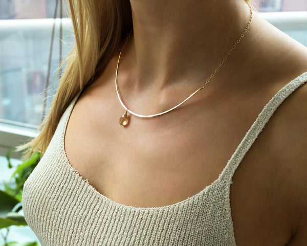 champagne quartz and thin delicate gold arc necklace on girls neck