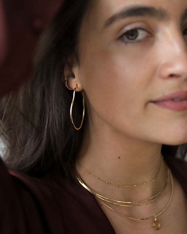 brunette wearing brass maeve thin hoop earrings champagne quartz gemstonce arc necklace and two 14k gold filled halo collars
