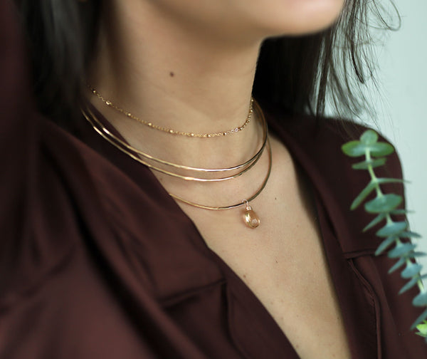 woman neck close up wearing 3 halo 14k gold filled collars with a champagne quartz gemstone and a ball chain choker necklace