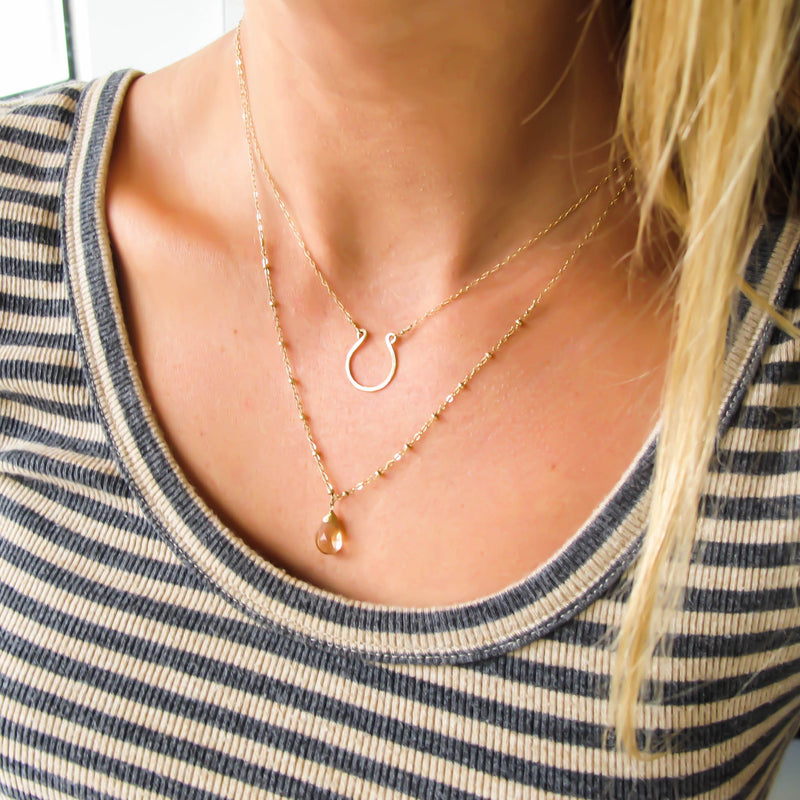 blond woman on a beige and grey stripes shirt wearing a 14k gold filled good luck horseshoe necklace