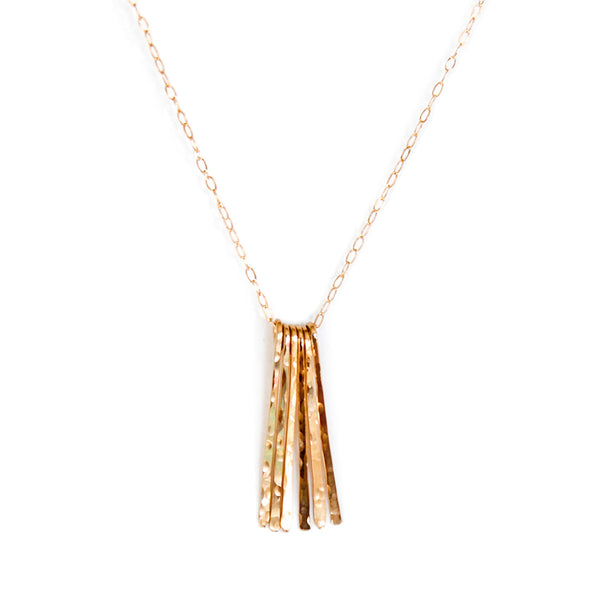 14k gold filled different strokes fringe pendant necklace on a white surface
