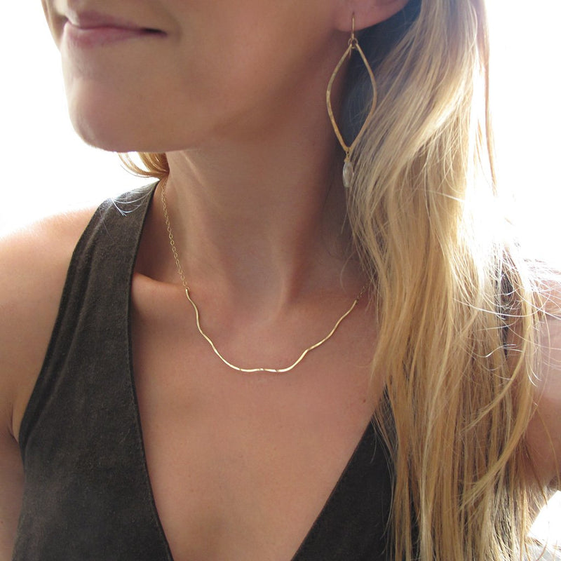 blond woman on a dark green top wearing a 14k gold filled coastal route necklace