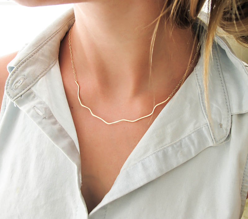 blond woman on a white shirt neck closeup wearing a 14k gold filled coastal route necklace