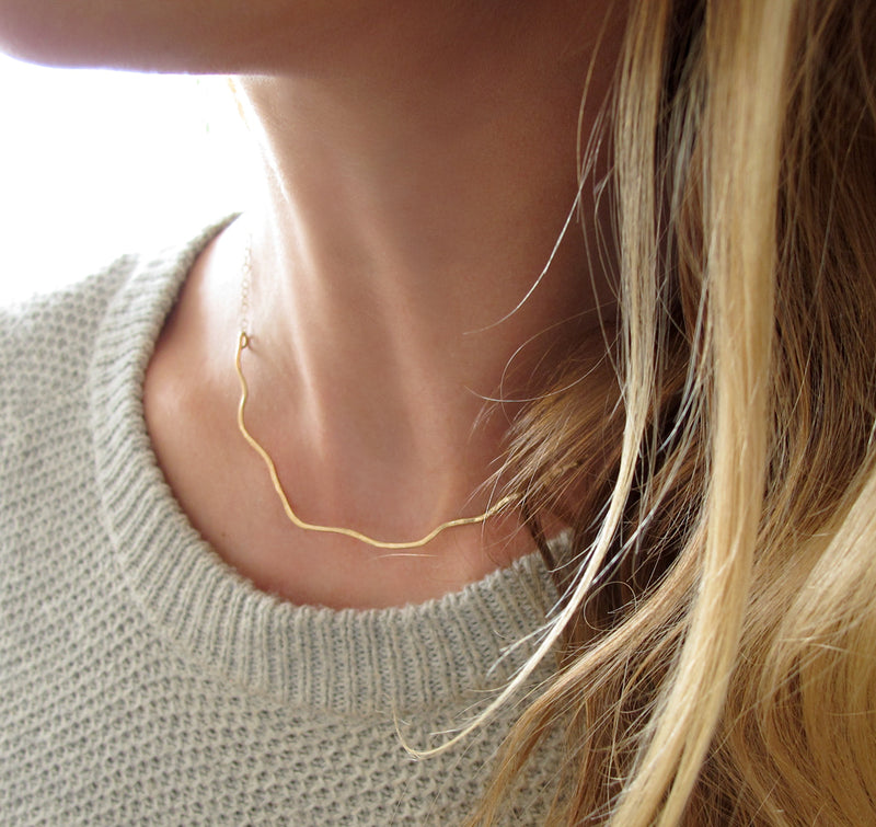 blond woman on a white sweater neck closeup wearing a 14k gold filled coastal route necklace