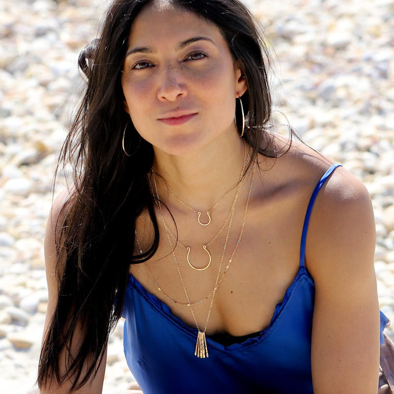 girl on beach with layered delicate gold necklaces and gold hoop earrings