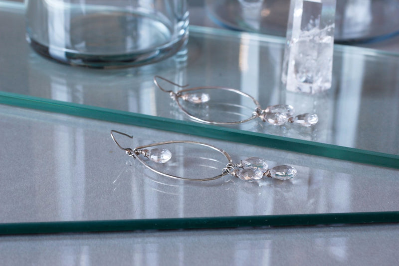 sterling silver crystal quartz dreamcatcher teardrop gemstone hoops laying on reflective glass surfaces