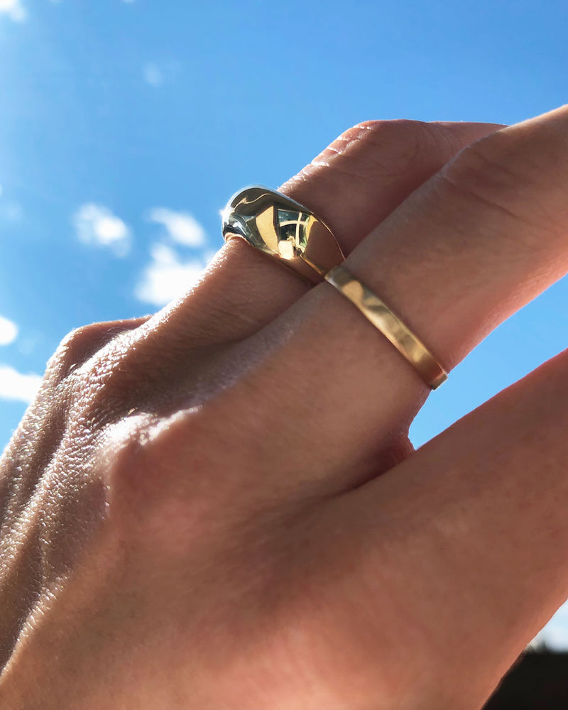 woman hand wearing curve ring on middle finger and hammered gold ring on ring finger against blue sky