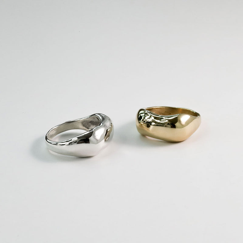 brass and sterling silver curve rings on white surface