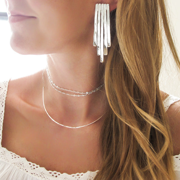 blond woman neck closeup wearing sterling silver empire earrings and a sterling silver xl scenic route necklace