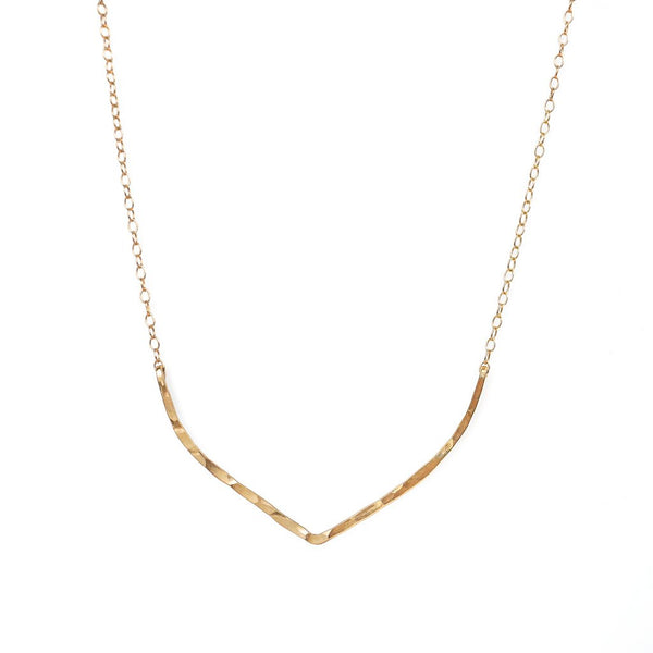 14k gold filled flight necklace on a white surface