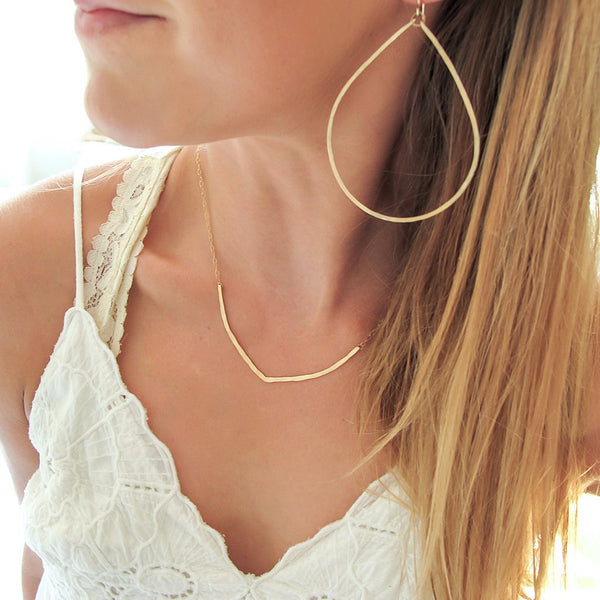 blond woman neck closeup wearing a white top with a 14k gold filled flight necklace