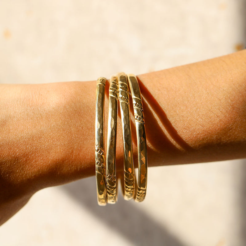 woman wrist close up wearing set of four florie bangles on white background under sunshine