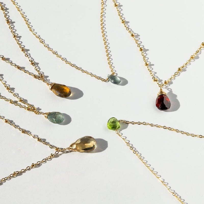 Beer moss aquamarine green amethyst champagne peridot and garnet beaded pendants and short gemstone necklaces on white surface