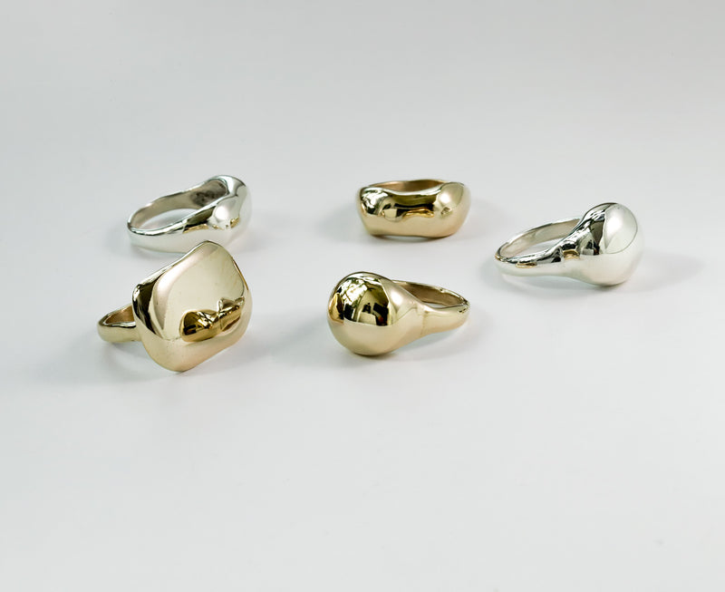 globe plateau and curve rings on silver and gold colors on white surface